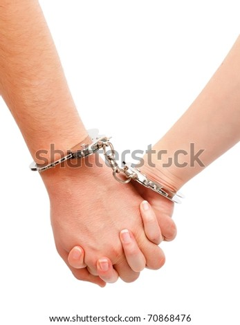 Couple's strong relation metaphor, hands linked with handcuffs - stock photo