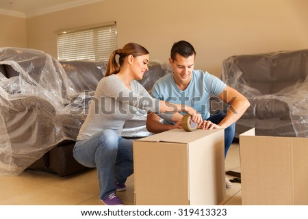 couple sealing moving boxes in their old home  - stock photo