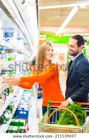Couple selecting dairy products grocery shopping in supermarket  - stock photo