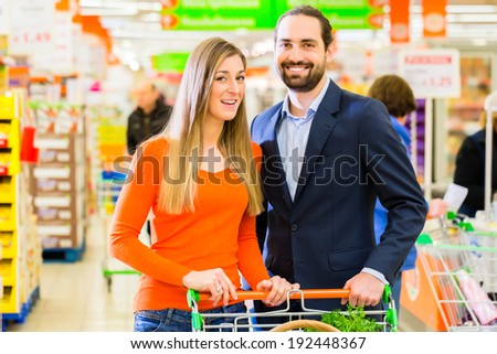 Couple selecting dairy products while grocery shopping in supermarket  - stock photo