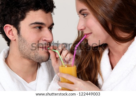 Couple sharing a glass of juice - stock photo