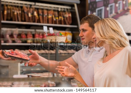 Couple shopping at the supermarket buying meat - stock photo