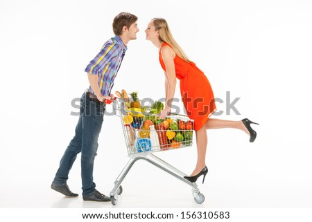 Couple shopping. Full length of couple standing near shopping cart and looking at each other while isolated on white - stock photo