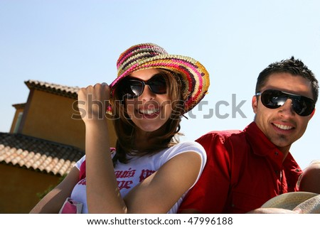 Couple showing off with sunglasses and hat on - stock photo