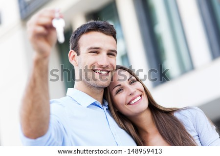 Couple showing their new house keys - stock photo