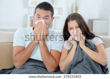 Couple sick on the sofa - stock photo