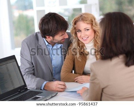 Couple signing property contract - stock photo