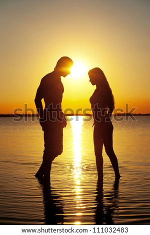 Couple silhouette at the beach at sunset. - stock photo