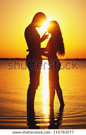 Couple silhouette at the beach. Sunset light. - stock photo