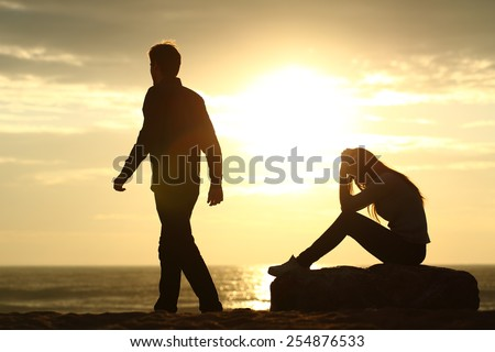 Couple silhouette breaking up a relation on the beach at sunset - stock photo