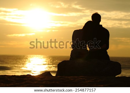 Couple silhouette cuddling and watching sun at sunset on the beach - stock photo