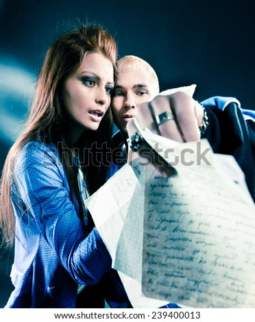 Couple sings hip-hop over dark background with spotlight - stock photo