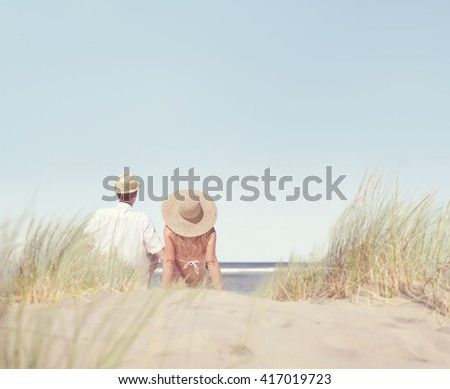 Couple Sitting and Looking at the View of the Beach - stock photo