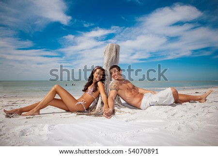 Couple sitting at a beach, happy - stock photo