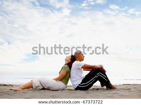 Couple sitting back to back at beach - stock photo