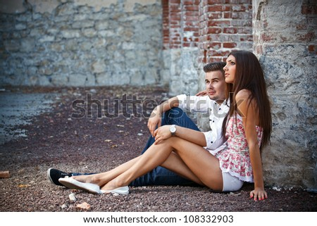 Couple sitting by brick wall - stock photo