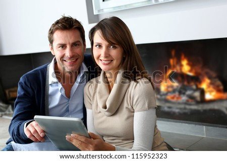 Couple sitting by fireplace and websurfing with tablet - stock photo