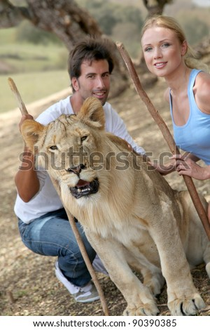 Couple sitting by lion in Savannah - stock photo