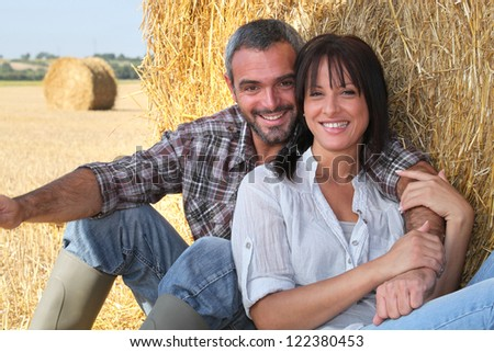 Couple sitting in front of hay bale - stock photo