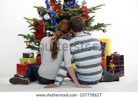 Couple sitting in front of their Christmas tree - stock photo