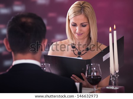 Couple Sitting In Restaurant Woman Choosing Menu - stock photo