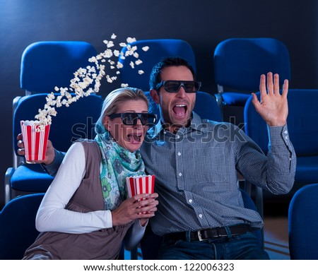 Couple sitting in seats at a cinema reacting in shock to a 3D movie throwing their hands up in horror sending their popcorn flying - stock photo