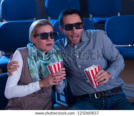 Couple sitting in seats at a cinema wearing 3D glasses reacting to the reality of the dimensional image in a scene in the movie - stock photo