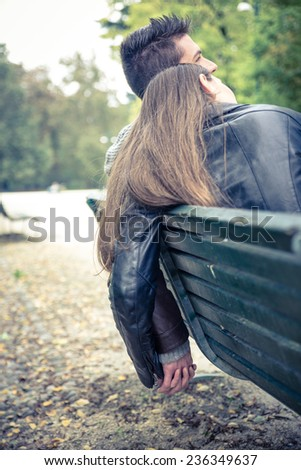 couple sitting on a bench and holding each other hands. concept about relationship and love - stock photo