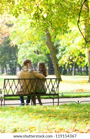 Couple sitting on a bench in park on a spring or fall day - stock photo