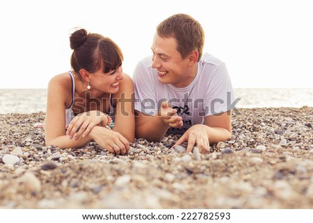 Couple sitting on a  sand seashore near sea looking at each other, relaxing on a vacation trip, looking on her husband. copy space - stock photo