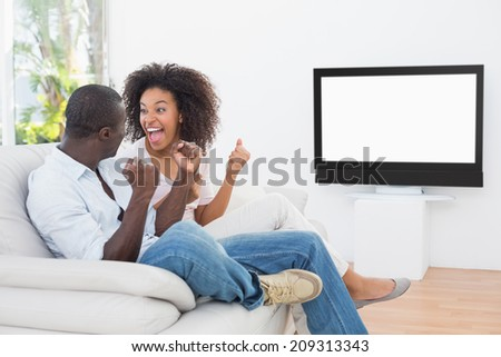 Couple sitting on couch together watching tv at home in the living room - stock photo