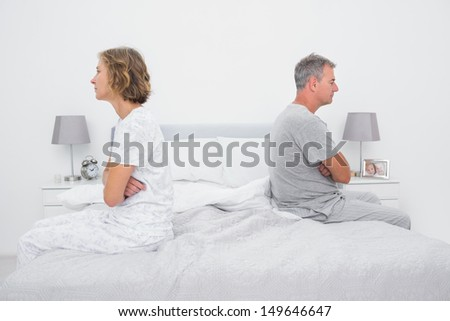 Couple sitting on different sides of bed not talking after dispute in bedroom at home - stock photo