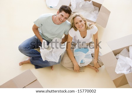 Couple sitting on floor by open boxes in new home smiling - stock photo
