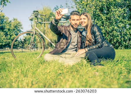 Couple sitting on grass and taking a selfie after a romantic tour with bicycle - Lovers looking at phone while relaxing in a park - stock photo
