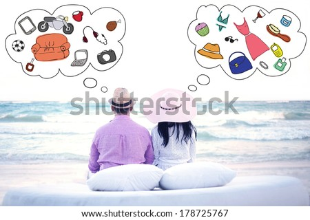 Couple sitting on the beach and thinking about different things - stock photo