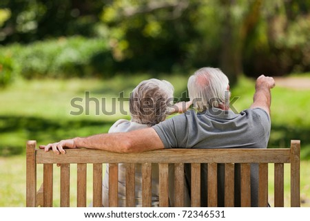 Couple sitting on the bench  with their back to the camera - stock photo