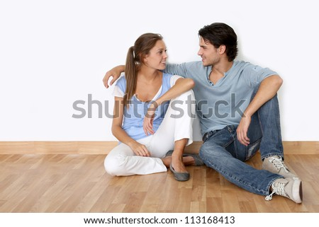 Couple sitting on the floor in new apartment - stock photo