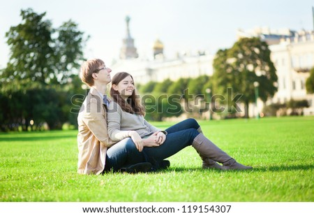 Couple sitting on the grass in Saint-Petersburg, Russia - stock photo
