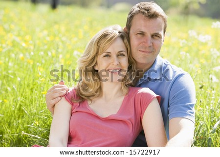 Couple sitting outdoors smiling - stock photo