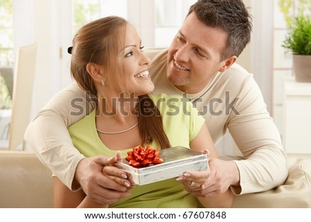 Couple sitting together laughing happily, woman holding present, man holding woman's hands.? - stock photo