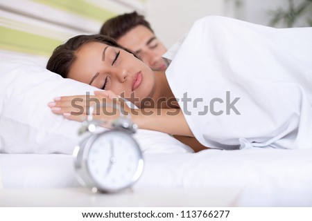couple sleeping together in bed with  alarm clock - stock photo