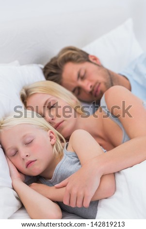 Couple sleeping with daughter in bed - stock photo