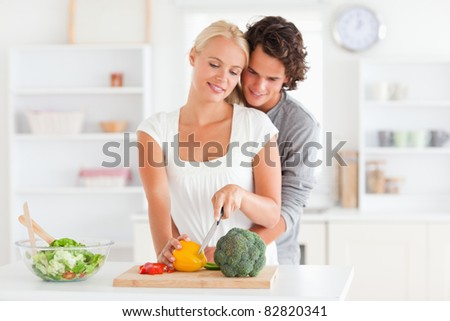 Couple slicing pepper in their kitchen - stock photo