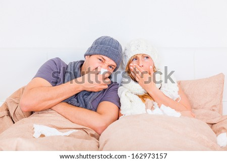 couple sneezing ill lying down - stock photo