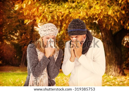 Couple sneezing in tissue against trees and meadow in the park - stock photo