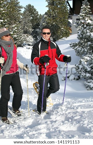 Couple snowshoeing - stock photo