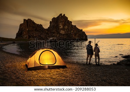 Couple stand at tent and Baikal lake shore and looking at the sunset - stock photo