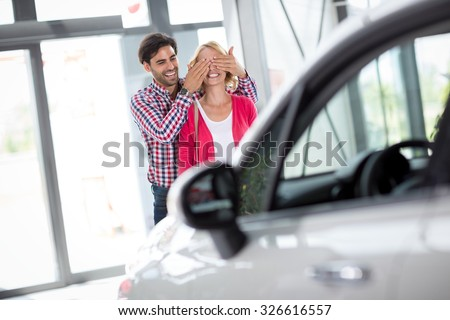 Couple stand in front of new car, man holding his wife covered her eyes  - stock photo