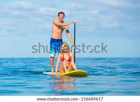 Couple Stand Up Paddle Surfing In Hawaii, Beautiful Tropical Ocean, Active Beach Lifestyle - stock photo
