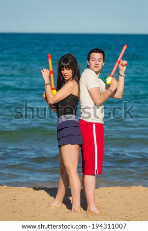 Couple standing back to back ready for a water pistol duel - stock photo